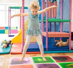 Child jumping on the sensory tiles at the Children's Respite Trust's Charity Day Centre in Sussex